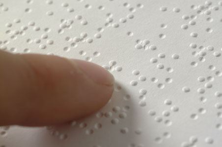 Fingers touching braille dots on a page