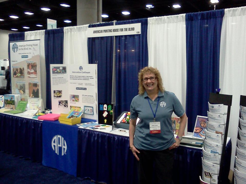 Kerry Isham standing beside APH's booth at the 2013 American Occupational Therapy Association; copyright 2013 APH