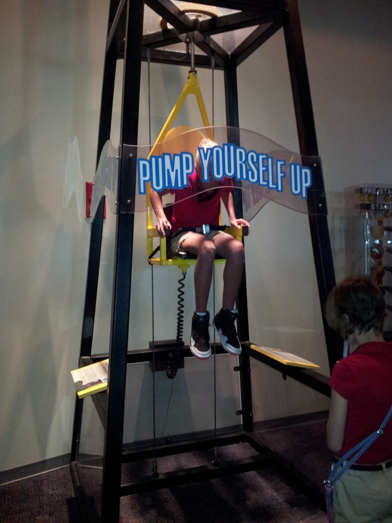 "Student sits in a chair and pumps air to boost herself into the air. A sign behind her reads, ""Pump yourself up!"""