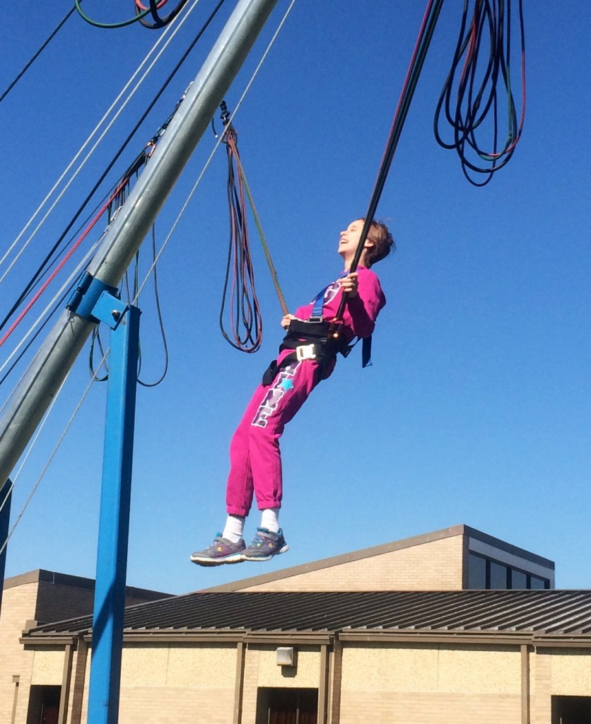 Lindsay jumping on a trampoline supported by bungee cords