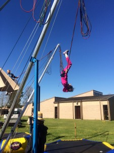 Lindsay upside down halfway through a flip on the bungee trampoline