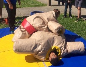 A student has pinned Lindsay to the ground in a sumo wrestling outfit