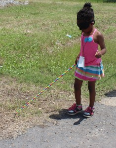 A first-grader walking with her cane along the shoulder of a quiet street