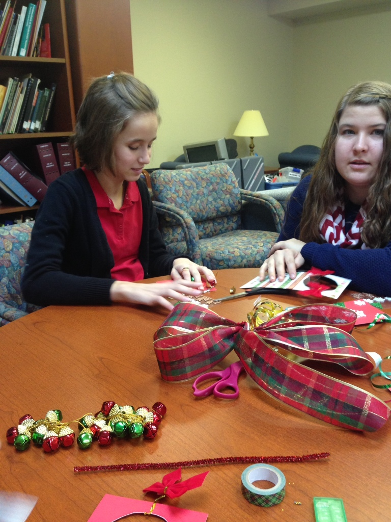 Students making decorative, holiday door hangers for the elderly
