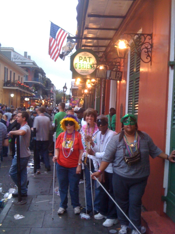 A group of students from the Louisiana Center for the Blind pose for a photo on a crowded street at Mardi Gras.