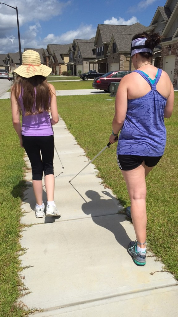 13-year-old Makayla leading the way down the sidewalk with her instructor, Joanne, following behind her