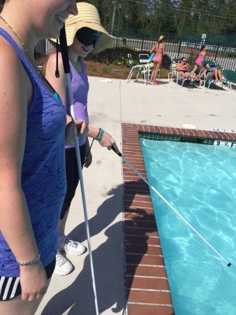 Jakayla finding the edge of the community pool with her cane