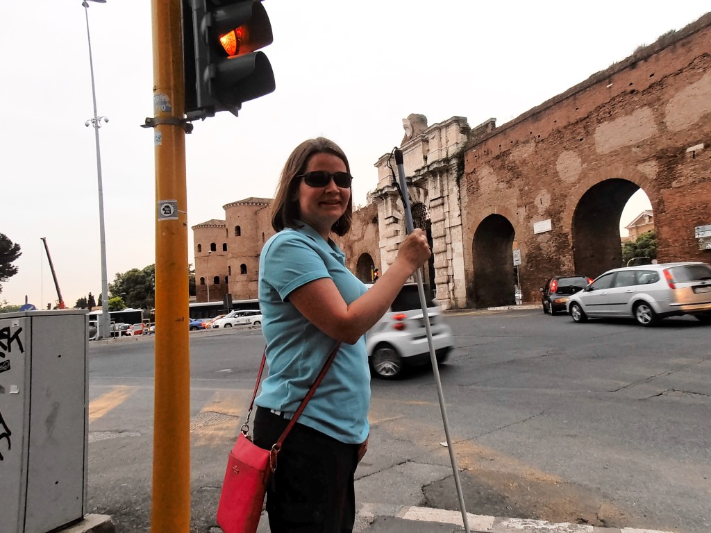 Jennifer Kennedy standing with her long white cane at the gate of Porta San Giovanni in the Aurelian Wall of Rome, Italy.