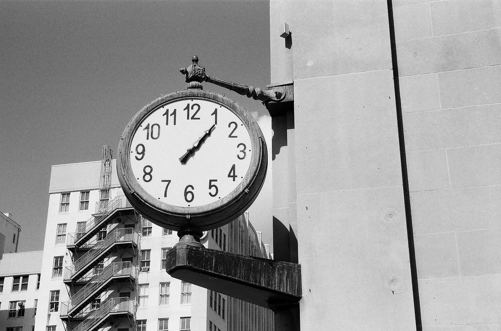 Large clock framed by a tall building in a big city; courtesy of Phillip Pessar, on Flickr